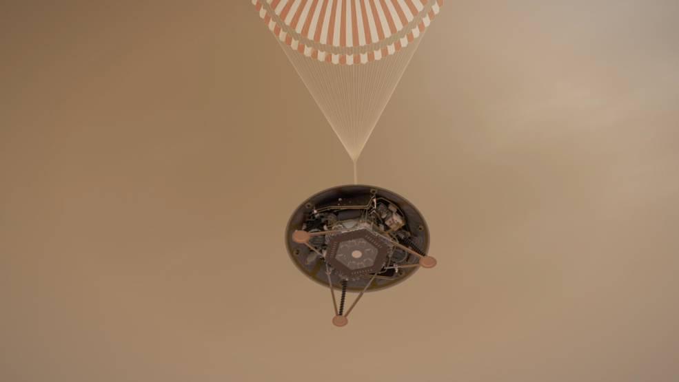 ilustración muestra una vista simulada del vehículo de aterrizaje InSight de la NASA que desciende en su paracaídas hacia la superficie de Marte.
