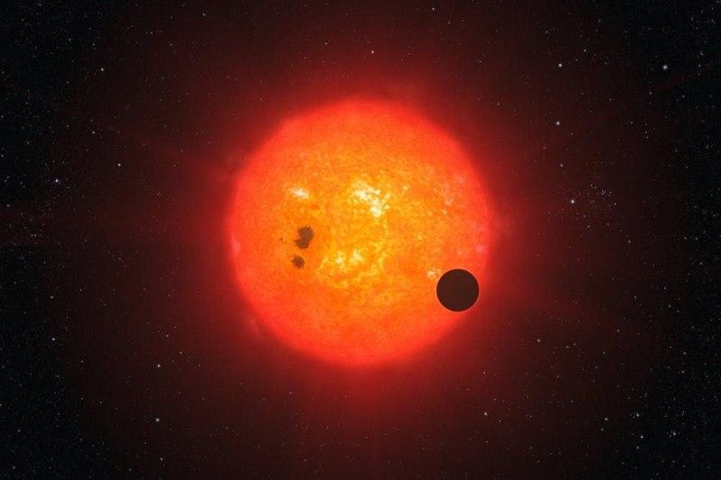 Impresión artística de un exoplaneta en tránsito por una estrella enana roja