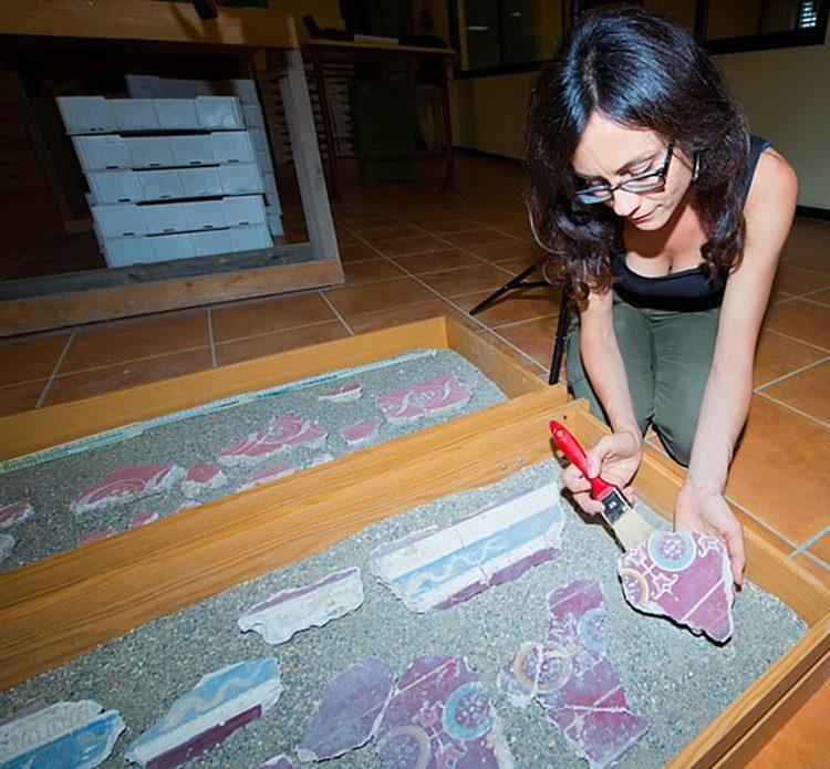 Una arqueóloga italiana reensamblando los frescos encontrados en el palacio de Calígula